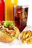 Hotdog com batatas fritas no guardanapo com vidro da cola Fotos de Stock