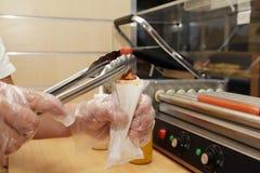 Hotdog in den Händen des Verkäuferfachmannes Stockbilder