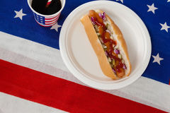 Hotdog diente in der Platte mit einem Getränk auf amerikanischer Flagge Stockfotografie
