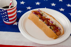 Hotdog diente in der Platte mit einem Getränk auf amerikanischer Flagge Stockfotos