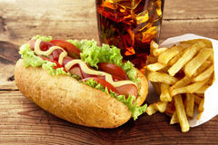 Hotdog with french fries on napkin with glass of cola Stock Photos