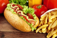 Hotdog with french fries on wooden plank Royalty Free Stock Images