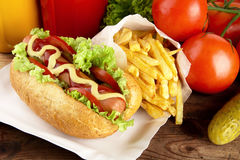 Hotdog with french fries on wooden plank Stock Images