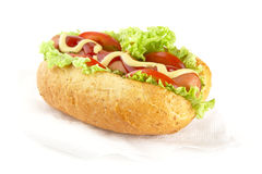 Hotdog with ingredients on serviette on white background Royalty Free Stock Photos