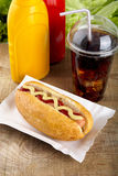 Hotdog with ketchup and mustard with cola on the wooden plank Stock Photo