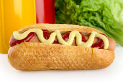 Hotdog with ketchup and mustard with salad in the background Stock Image