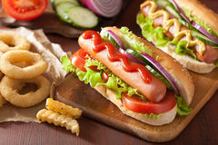 Hotdog with ketchup mustard vegetables and french fries Royalty Free Stock Image