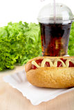 Hotdog with lettuce in the background with cola on wooden desk Stock Photo