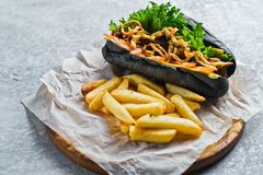 Hotdog met rundvleesworst en gekarameliseerde uien in een zwart broodje Grijze achtergrond, hoogste mening, ruimte voor tekst stock fotografie