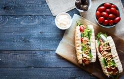 Hotdog mit Essiggurken, Tomaten und Oliven Stockfotografie