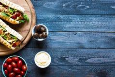 Hotdog mit Essiggurken, Tomaten und Oliven Stockfoto