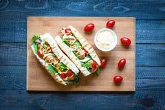 Hotdog mit Essiggurken, Tomaten und Oliven Stockbild
