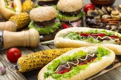 Hotdog mit gebratenem Mais, Hamburgern, Tomate und gebackenem Gemüse auf einem hölzernen Hintergrund lizenzfreies stockfoto