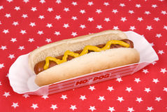 Hotdog with mustard in patriotic tablecloth. A cooked hotdog with mustard on a patriotic tablecloth Royalty Free Stock Images