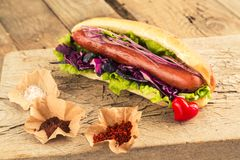 Hotdog with sausage and seasonings. Hotdog with sausage and seasonings for fast food lovers. Homemade snack with grilled sausage and onion stock photos