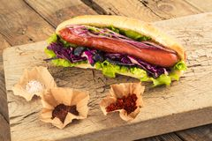 Hotdog with sausage and seasonings. Hotdog with sausage and seasonings for fast food lovers. Homemade snack with grilled sausage and onion stock image