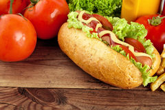 Hotdog with tomatoes in the background on wooden plank Royalty Free Stock Photos