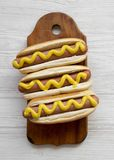 Hotdog with yellow mustard on rustic board on white wooden surface, top view. Flat lay, overhead, from above stock photo