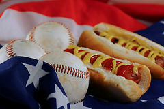 Hotdogs & Baseballs on an american flag. Background royalty free stock images