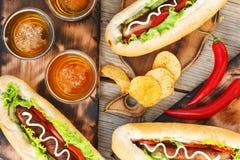 Hotdogs, chiper och kraft öl, bästa sikt Royaltyfri Foto