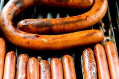 Hotdogs die op de openluchtgrill sissen Stock Fotografie