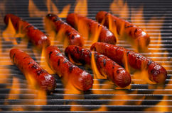 Hotdogs on a Flaming Hot Barbecue Grill. Hotdogs cooking on a barbecue grill with hot flame Stock Photo