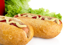 Hotdogs with ketchup with lettuce in the background on white Royalty Free Stock Photos
