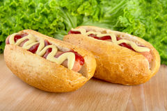 Hotdogs with mustard and ketchup with lettuce in the background on wooden desk Stock Photography