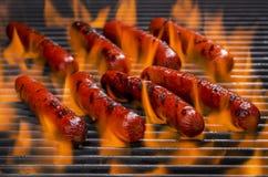 Hotdogs på ett flammande varmt grillfestgaller Arkivfoto