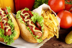 Hotdogs on plate with cola, french fries on wooden desk Royalty Free Stock Image