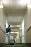 Hotel. A man with a suitcale is walking down a hotel hallway Stock Image