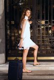 At the hotel. Girl entering the hotel with the suitcase stock image