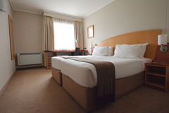 Hotel accommodation. Clean, neat but very basic three star hotel accommodation. A room with writing desk, air conditioning unit, two single beds placed together stock photography