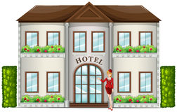 A hotel attendant standing in front of the hotel Stock Photo