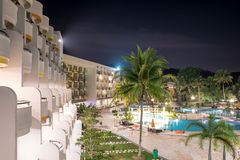 Hotel balcony side view of a hotel resort during night with swimming pool and bright lights reflecting on blue swimming pool water royalty free stock photography