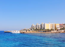 Hotel on bank of blue sea. Egypt, Hurghada royalty free stock photo