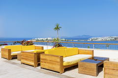 Hotel bar  with sea view and yellow  sofas. Outdoor bar with wooden sofas and sea view Royalty Free Stock Image