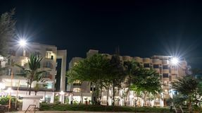 Hotel in a beach resort during night with bright lights and trees with clear sky and stars stock images