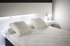 Hotel_bed. Closeup of a modern hotel double bed with white sheets and a reading lamp Stock Photography