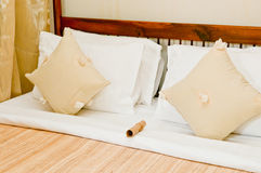 The Hotel Bed. A detail of a luxurious resort bed with silk covers and pillows stock photo