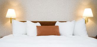 Hotel bed. Made up bed in a hotel room with night lamps Royalty Free Stock Photos