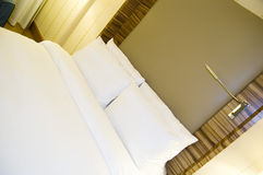 Hotel Bed. Closeup of a modern hotel double bed with white sheets and a reading lamp Royalty Free Stock Photo