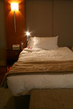 Hotel bed. With reading light on Royalty Free Stock Photography