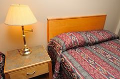 Hotel bed and lighted lamp Royalty Free Stock Photos