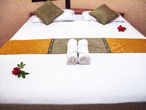 Hotel bed with white linen. Decorated hotel bed with white linen in a bungalow Royalty Free Stock Images