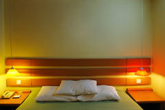 Hotel bedroom. Nicely decorated hotel bedroom in the lamplight royalty free stock images