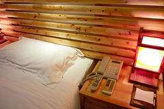 Hotel bedroom. Image of a hotel bedroom with wooden bed and lamp,telephone and remote control ,.in dujiangyan,sichuan,china royalty free stock image
