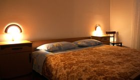 Hotel bedroom. A shot of hotel bedroom with illuminated lights Royalty Free Stock Photography