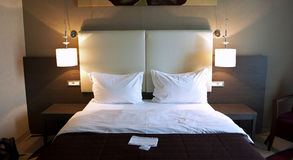 Hotel bedroom. Luxurious suite with leather decorated bed royalty free stock images