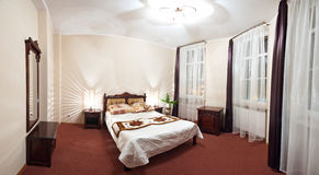 Hotel bedroom. Elegant interior of a cosy classic hotel bedroom royalty free stock images